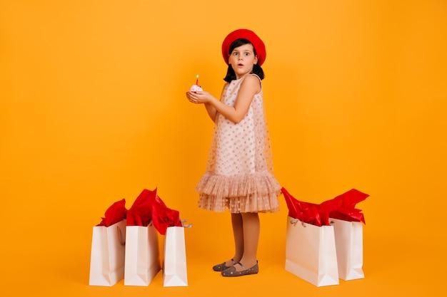 Plan Complet D'une Petite Fille Avec Des Sacs à Provisions. Mignon Enfant En Béret Français Rouge Isolé Sur Mur Jaune. Photo gratuit