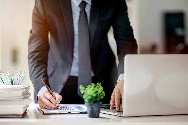 Plan d'un homme d'affaires travaillant avec un ordinateur portable et des documents au bureau Photo Premium