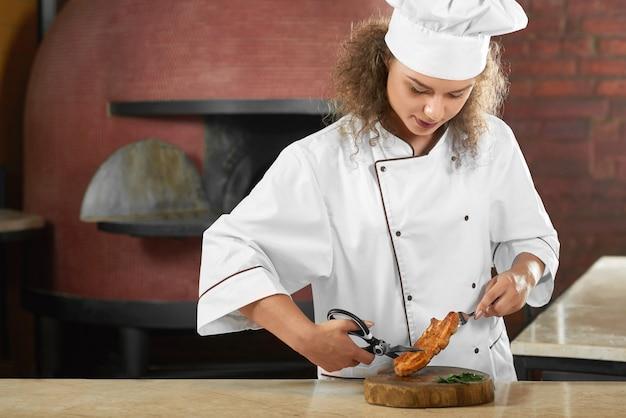 Plan Horizontal D'une Belle Femme Chef Cuisinier à La Cuisine Du Restaurant Coupe De La Viande Grillée Avec Des Ciseaux Copyspace Profession Profession Emploi Carrière Employé. Photo gratuit