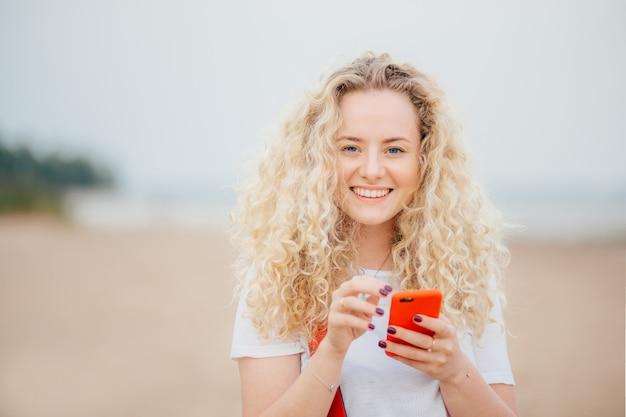 Plan Horizontal D'une Belle Jeune Femme Blonde Aux Cheveux Bouclés, Avec Un Téléphone Intelligent Orange. Photo Premium