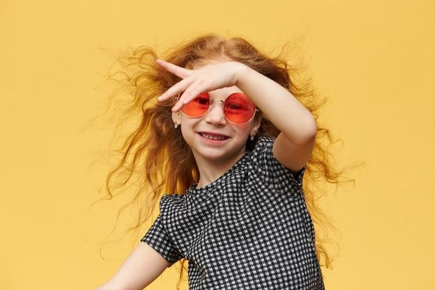 Plan Horizontal De La Belle Petite Fille Branchée Heureuse Aux Cheveux Bouclés Roux Appréciant La Danse, Avec Un Large Sourire Joyeux, Portant Des Lunettes De Soleil. Concept De Musique, Danse, Amusement Et Enfants Photo gratuit