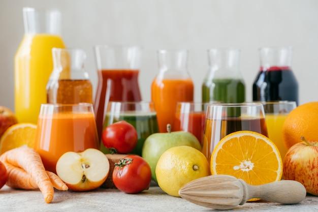 Plan horizontal de fruits et légumes frais sur une table blanche, de pots en verre de jus et d'un presse-agrumes. Photo Premium