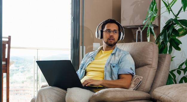 Plan Horizontal D'un Homme écoutant De La Musique Avec Des écouteurs Et Un Ordinateur Portable Sur Les Genoux Photo gratuit