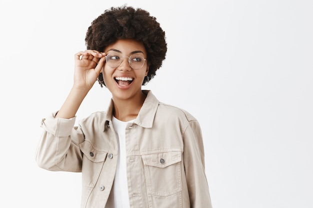 Plan Horizontal De Lesbiennes Confiantes Insouciantes Afro-américaines à Lunettes Et Chemise Beige Touchant Le Bord Des Lunettes Et Regardant à Droite, Souriant Largement Confiant Et Heureux Photo gratuit