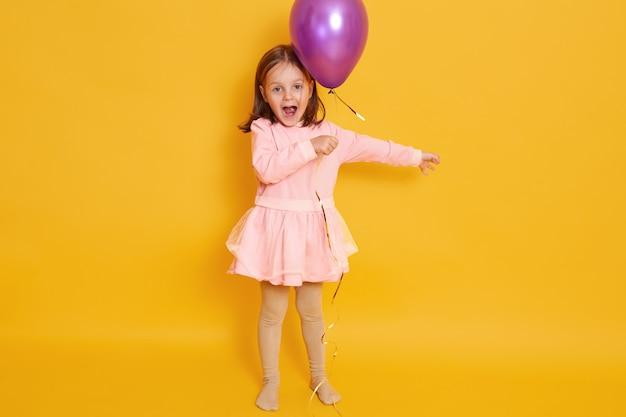 Plan Horizontal De Petite Fille Avec Un Ballon Violet Isolé Sur Jaune Tous Les Enfants De Sexe Féminin Criant Quelque Chose, Célébrant Herbirtday, Kid Portant Une Robe Rose Et Ayant Les Cheveux Noirs. Photo gratuit