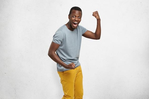 Plan Intérieur D'un Beau Jeune étudiant Afro-américain Chanceux Excité S'exclamant D'excitation Photo gratuit