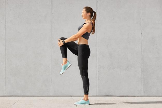 Plan D'une Jeune Femme Flexible Se Réchauffe Avant De Faire Du Jogging Sur Le Stade Photo Premium