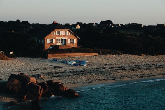 Plan Large D'une Maison Brune Sur Une Plage De Sable Au Bord De La Mer Entourée De Rochers Et D'arbres Photo gratuit