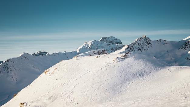 Plan Large De Montagnes Couvertes De Neige Sous Un Ciel Bleu Clair Avec Une Demi-lune Photo gratuit
