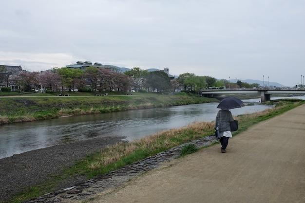 Plan Large D'une Personne Avec Un Parapluie Se Promène Le Long De La Rivière Kamo à Kyoto, Japon Photo gratuit