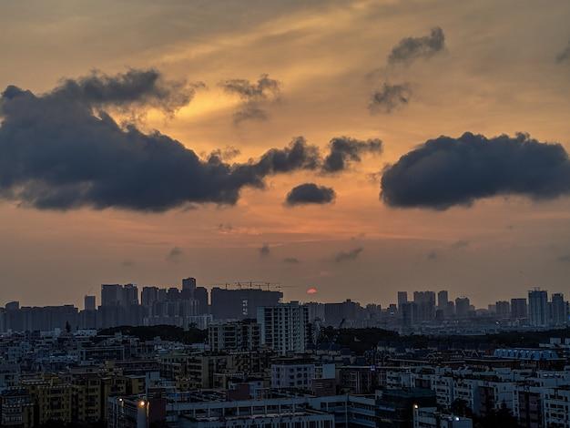 Plan Large D'une Ville Moderne Et Animée Avec Des Nuages Sombres Et Un Ciel Orange Photo gratuit