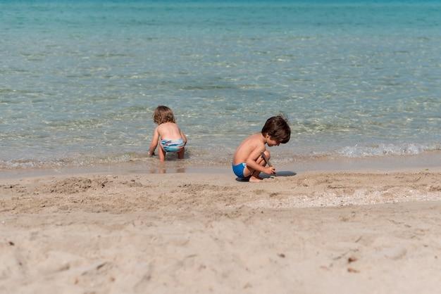 Plan long d'enfants jouant à la plage Photo gratuit
