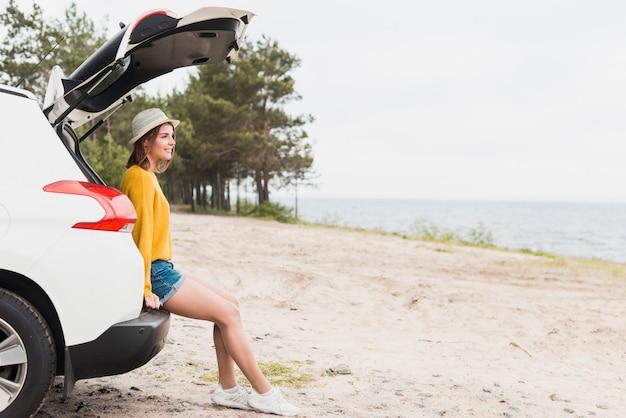 Plan long de la femme en voyage et de sa voiture Photo gratuit