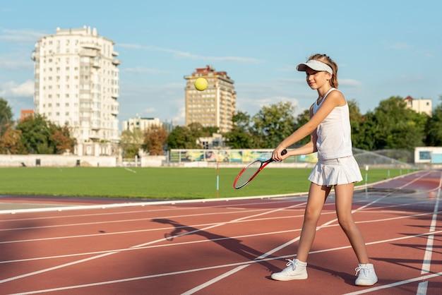 Plan long d'une fille jouant au tennis Photo gratuit