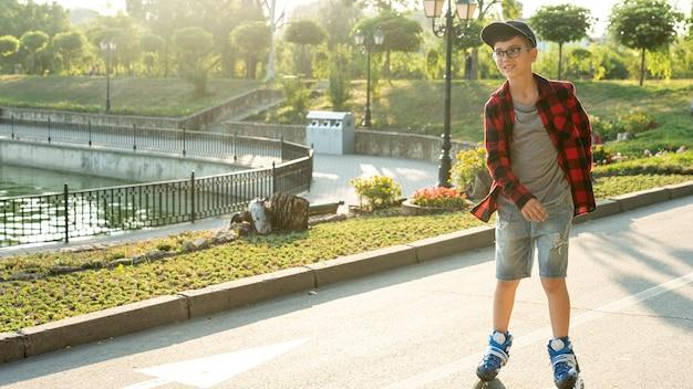 Plan long d'un garçon avec des patins à roues alignées Photo gratuit
