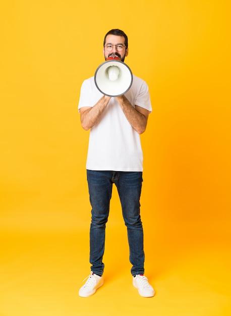 Plan long d'un homme à la barbe sur fond jaune isolé criant à travers un mégaphone Photo Premium