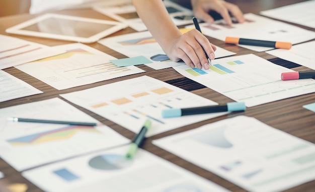 Plan de la main de l'homme travaillant avec un graphique ou un document graphique au bureau Photo Premium