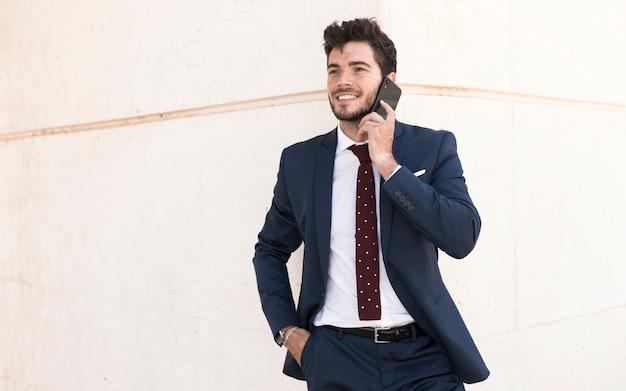 Plan moyen adulte en costume parlant au téléphone Photo gratuit