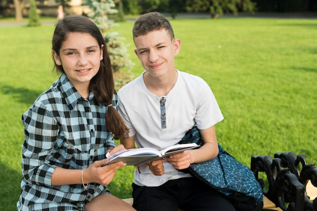 Plan moyen d'amis lycéens partageant un livre sur un banc Photo gratuit