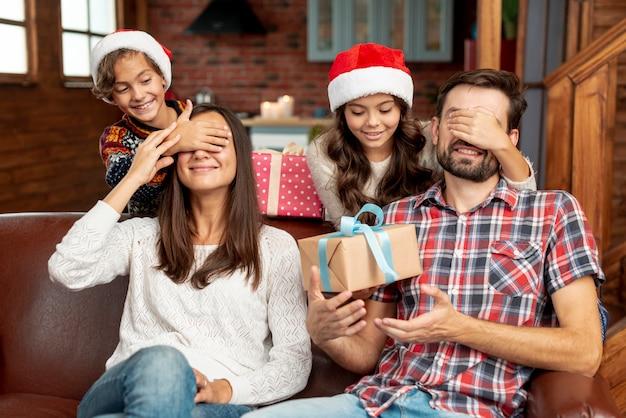 Plan moyen enfants surprenant parents avec des cadeaux Photo gratuit