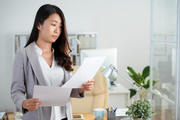Plan moyen de femme asiatique vérifiant des documents commerciaux Photo gratuit