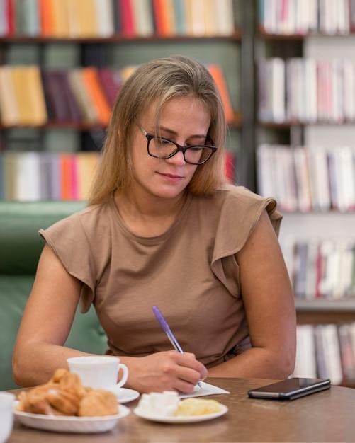 Plan Moyen Femme Dans L'écriture De La Bibliothèque Photo gratuit