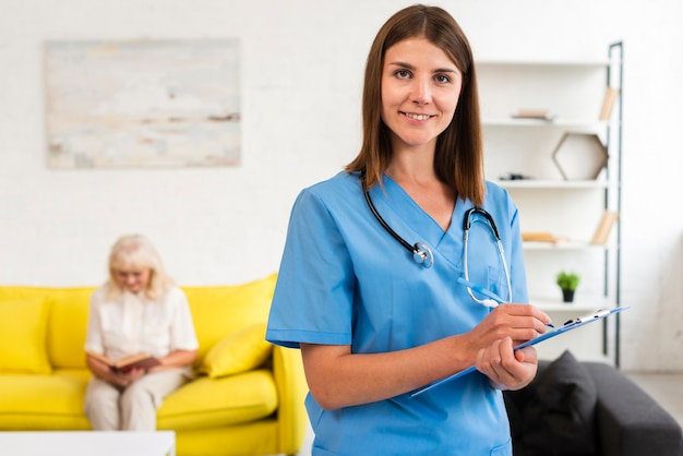 Plan Moyen Femme Médecin Avec Le Presse-papier Bleu En Regardant La Caméra Photo gratuit