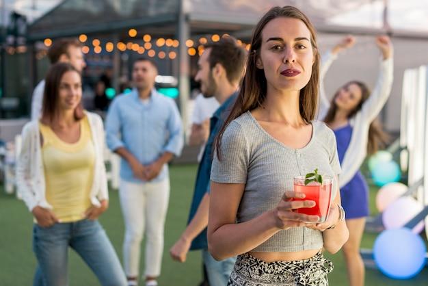Plan moyen femme posant avec un cocktail Photo gratuit