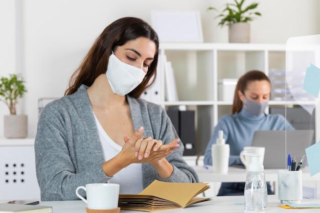 Plan Moyen Femme Utilisant Un Désinfectant Photo Premium