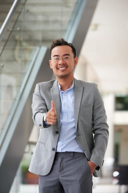 Plan moyen d'un homme asiatique donnant un coup de pouce à la caméra Photo gratuit
