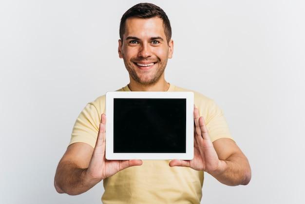 Plan moyen homme montrant une maquette de tablette Photo gratuit