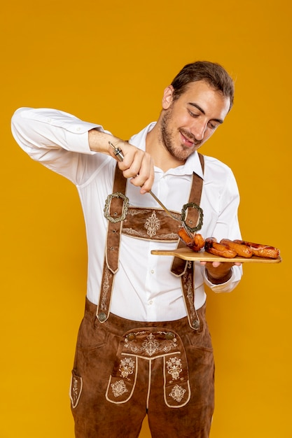 Plan moyen d'un homme avec un plateau de saucisses Photo gratuit