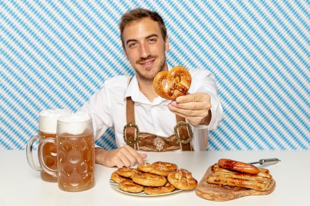 Plan moyen d'un homme tenant un bretzel allemand Photo gratuit