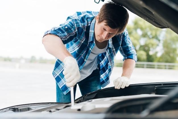 Plan moyen d'un homme travaillant sur une voiture Photo gratuit