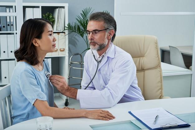 Plan moyen d'un médecin examinant la patiente avec un stéthoscope Photo gratuit