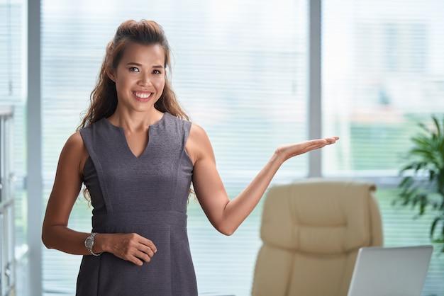 Plan moyen d'un modèle asiatique gesticulant comme s'il présentait un produit dans une publicité Photo gratuit