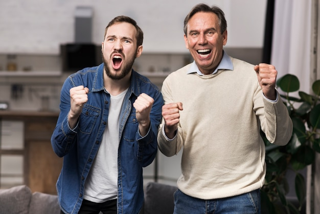 Plan Moyen Père Et Fils Acclamant Dans Le Salon Photo gratuit