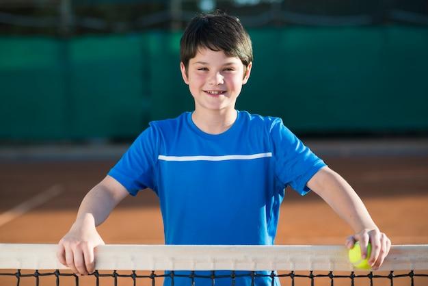 Plan moyen portrait d'enfant sur le terrain de tennis Photo gratuit