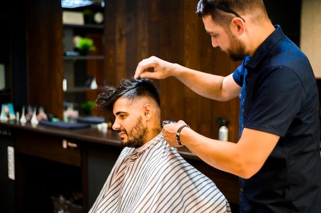 Plan moyen d'une styliste arrangeant les cheveux du client Photo gratuit