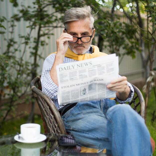 Plan Moyen Vieil Homme Lisant Le Journal Photo gratuit