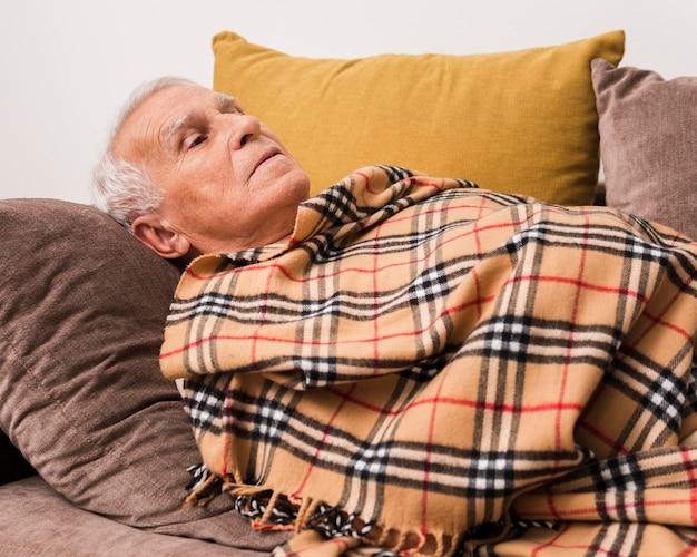 Plan Moyen Vieil Homme Portant Sur Le Canapé Photo gratuit