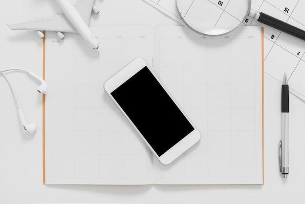 Plan plat de planification de voyage avec smartphone écran blanc et planificateur d'itinéraire de voyage sur fond blanc Photo Premium