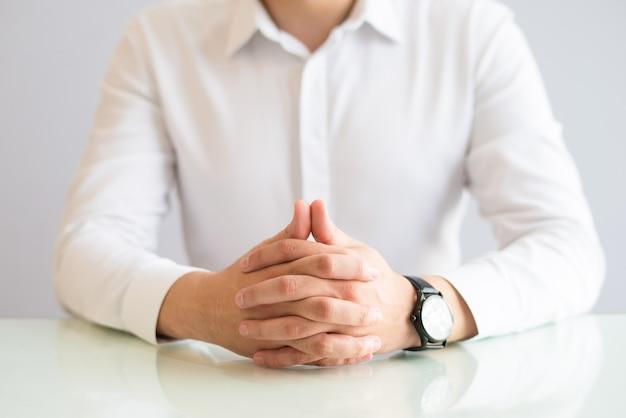 Plan rapproché d'un homme assis à table avec ses mains jointes Photo gratuit