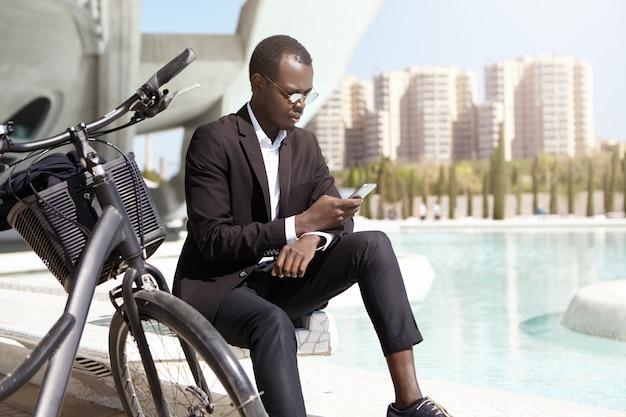 Plan Urbain D'un Homme D'affaires Afro-américain Confiant Portant Des Lunettes De Soleil Rondes Et Un élégant Costume Noir Assis à L'extérieur Avec Son Vélo, à L'aide D'un Téléphone Portable, En Vérifiant Les E-mails Et En Traitant Les Problèmes Commerciaux Photo gratuit