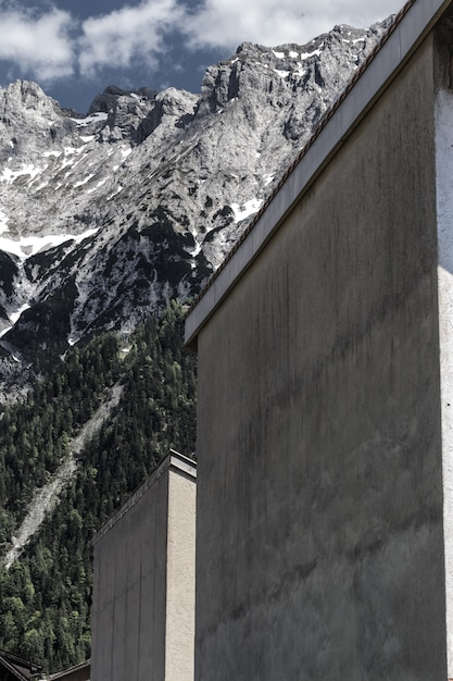 Plan Vertical De Bâtiments Gris Près De Montagnes Entourées D'arbres Photo gratuit