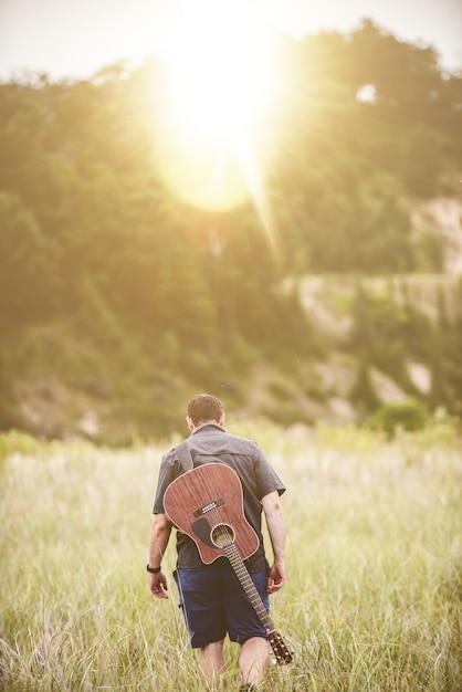 Plan Vertical D'un Homme Marchant Dans Un Champ à Côté D'une Forêt Avec Une Guitare Sur Le Dos Photo gratuit