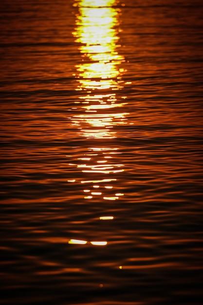 Plan Vertical Des Vagues De La Mer Reflétant La Lumière Du Soleil Au Coucher Du Soleil Photo gratuit