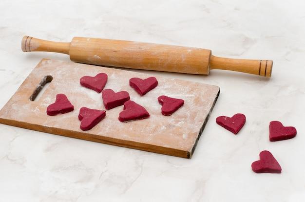 Planche de bois avec des coeurs rouges en pâte. la saint valentin Photo Premium