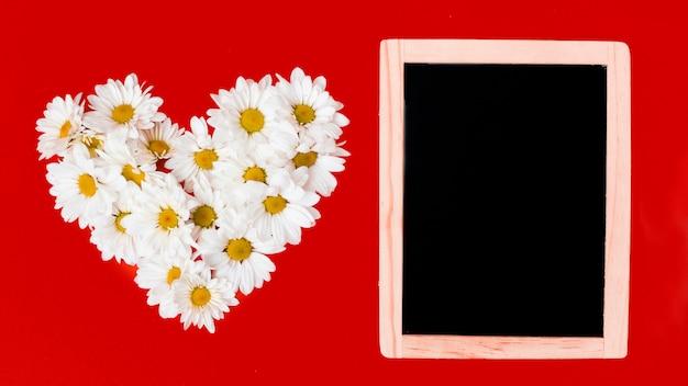 Planche de bois et fleurs de marguerite en forme de coeur Photo gratuit