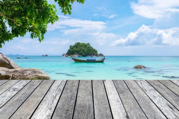 Planche de bois gris sur une mer de cristal avec un bateau à longue queue Photo Premium